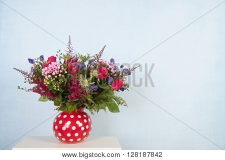 Vase mixed bouquet flowers on blue background