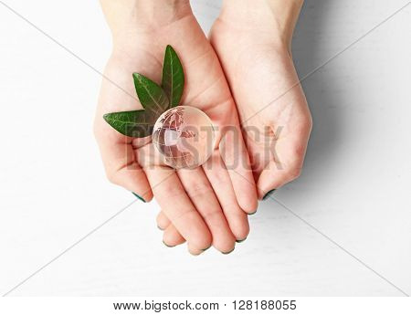 Female hands holding small glass globe over wooden table, top view