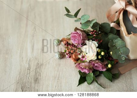 Bouquet of roses and ballet shoes on wooden background