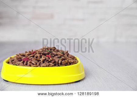 Bowl with dog food on the floor in front of brick wall background