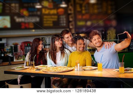 Cheerful multiracial friends taking selfie in pizzeria.