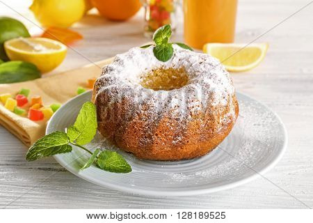 Delicious citrus cake with fruits on wooden table