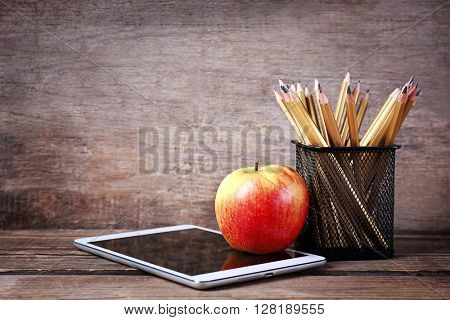 Set of pencils in metal holder, tablet and apple on wooden background