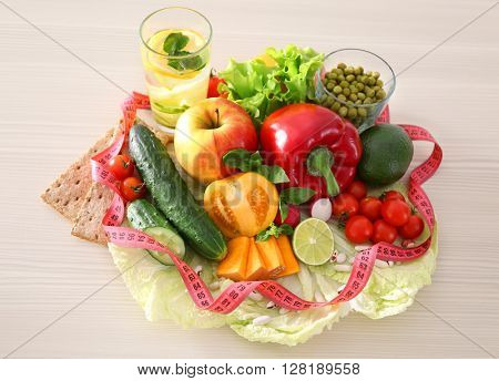 Fresh fruits and vegetables with measuring tape on wooden background
