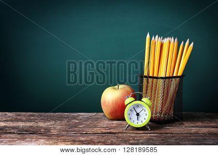Set of pencils in metal holder, alarm clock and apple on blackboard background