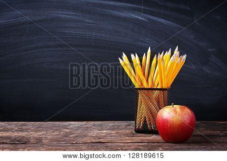 Set of pencils in metal holder and apple on blackboard background