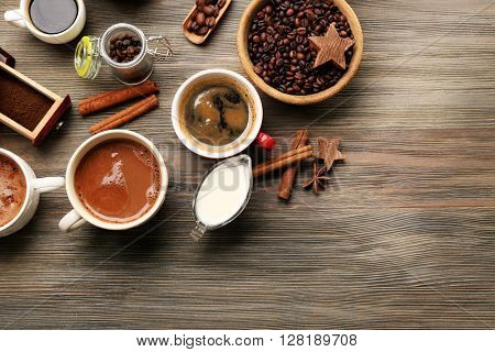 Assorted fresh coffee with spices on wooden table, top view