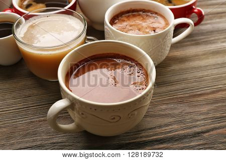 Different cups of coffee on wooden table closeup