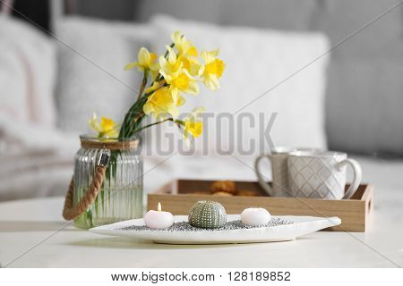 Bouquet of narcissus and candles on table indoors