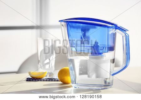 Water filter jug with lemon and glass on light wooden table