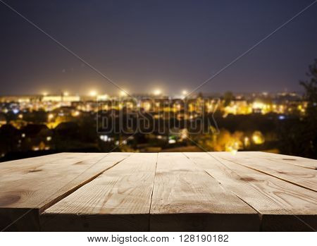 Night city and wooden table