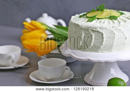 Lime cake with white tableware and bouquet of flowers