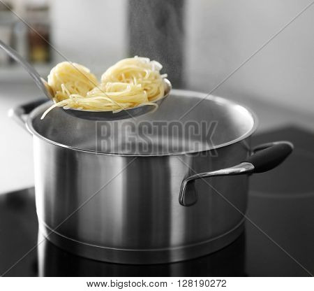 Spaghetti in strainer over the pan on stove closeup