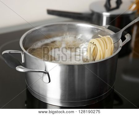 Spaghetti rolled on fork over pan closeup