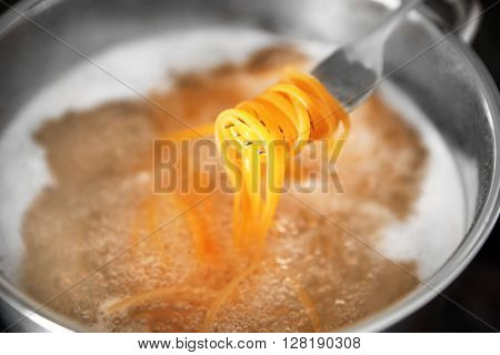 Pasta rolled on fork over pan on stove closeup