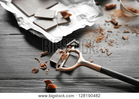 Piece of chocolate with peeler on black wooden background