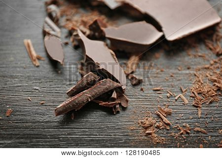 Pieces of chocolate on black wooden background