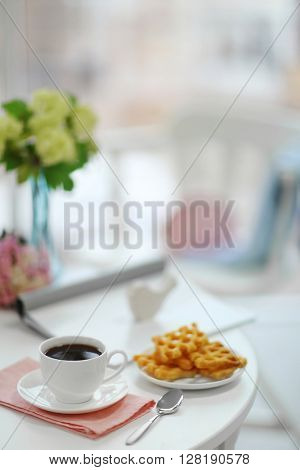 White cup of the coffee and sweets on wooden table  in a light room.