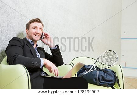 Happy businessman using smart phone while changing his clothes for match in squash. Happy man sitting on chair on squash court. ** Note: Soft Focus at 100%, best at smaller sizes