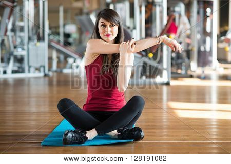 Beautiful woman doing stretching in a gym