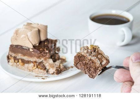 hand holding a fork with a piece of cake