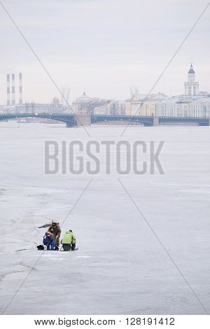 St. Petersburg, Russia - on March, 13, 2016: Fisherman on an ice of Neva river in St. Petersburg, Russia.