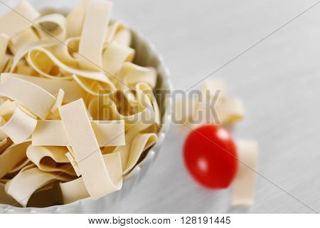 Bowl of uncooked pasta on wooden table closeup