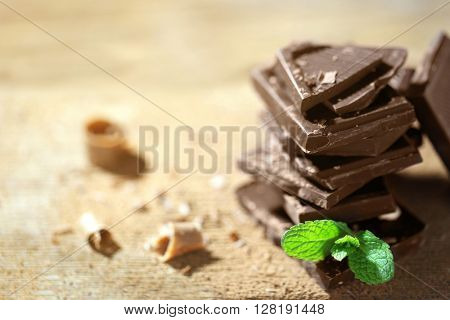 Stack of black chocolate pieces with fresh mint on wooden table
