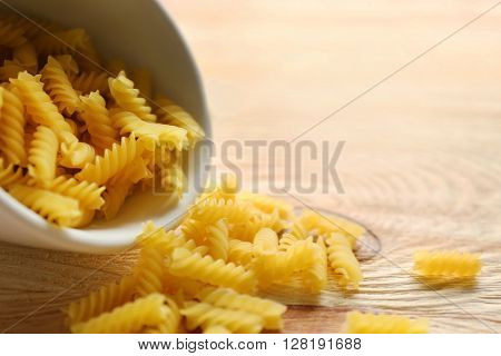 Dry fusilli pasta in white bowl on wooden table