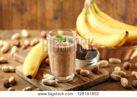 Fresh banana cocktail with peanuts and chocolate on wooden table
