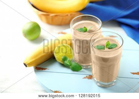 Banana cocktail and fresh fruits on wooden table