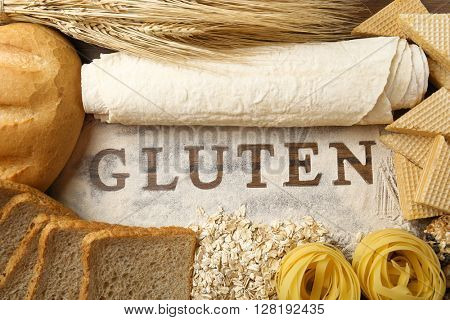 The word GLUTEN and flour products on wooden surface closeup