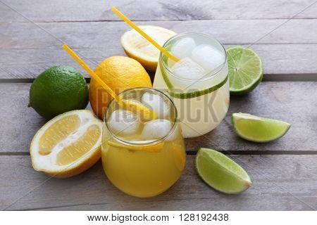 Glasses of lemon soda with ice on rustic wooden background