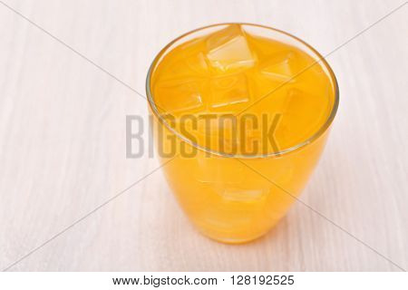 Glass of orange juice with ice on light wooden background