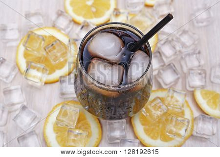 Glass of cola with ice and lemon on light wooden table