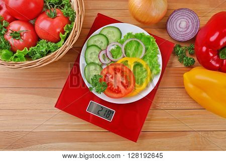 Plate with sliced fresh vegetables on digital kitchen scales over wooden background