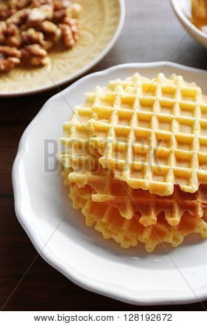 Waffles with walnuts and honey on wooden background