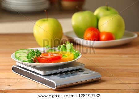 Plate of sliced fresh vegetables and digital kitchen scales on wooden table