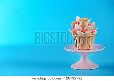 Tasty cupcake with beautiful decoration on blue background