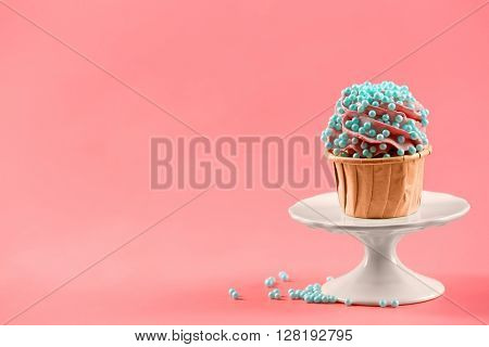 Tasty cupcake with original decoration on pink background