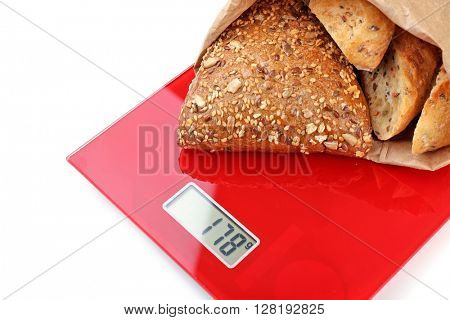 Tasty bread on digital kitchen scales, isolated on white