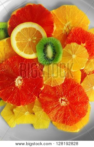 Plate of fresh peeled and sliced citrus, top view