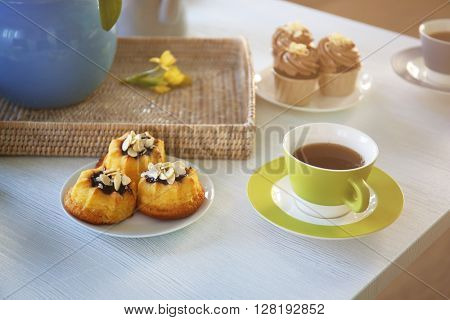 Cups of tea and cakes on wooden background