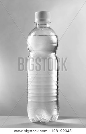 Bottled water on the grey background, close up