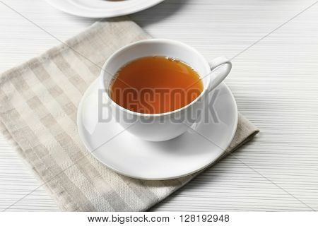 Hot black tea in a cup on a napkin