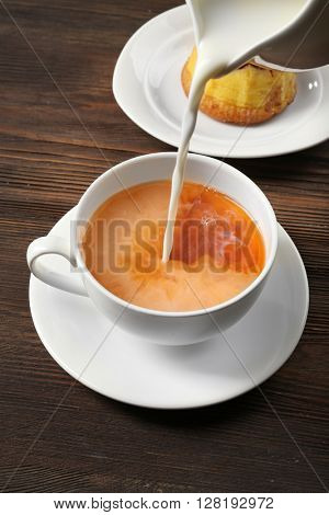 Milk poured into a cup of tea on wooden background.