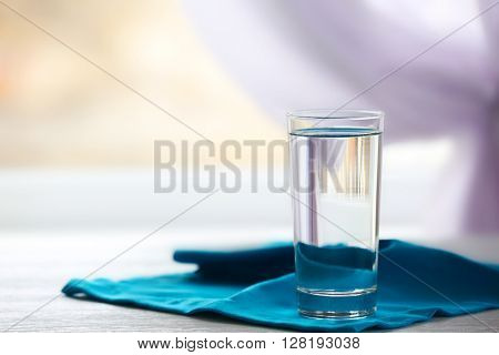 Glass of water on a blue napkin, close up