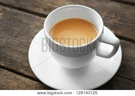 Cup of tea with milk on wooden background