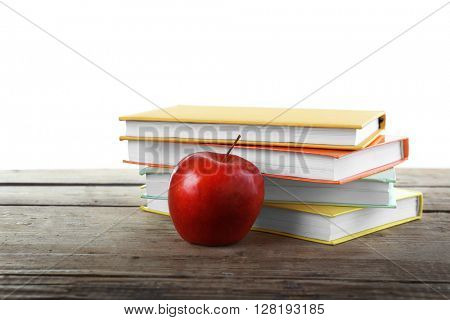 Few books with red apple on table