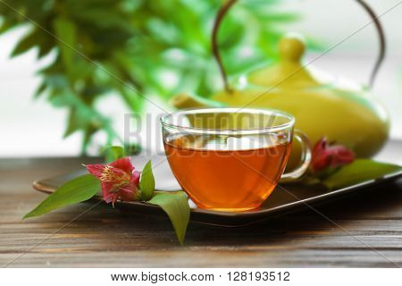 Glass cup of tea with teapot on wooden table against blurred background